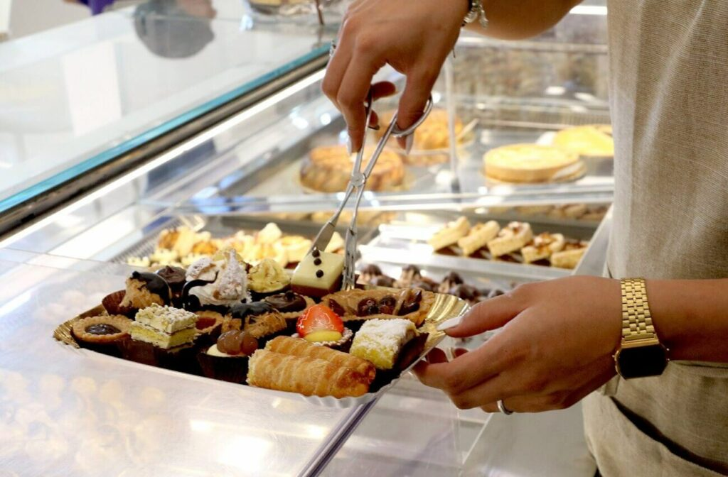 Detalhe de mão feminina servindo-se em uma padaria | Club Coworking - Padaria no Itaim Bibi