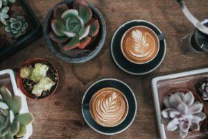 Duas xícaras de café com latte art sobre uma mesa acompanhada de vasos de plantas | Cafés na Paulista - Club Coworking