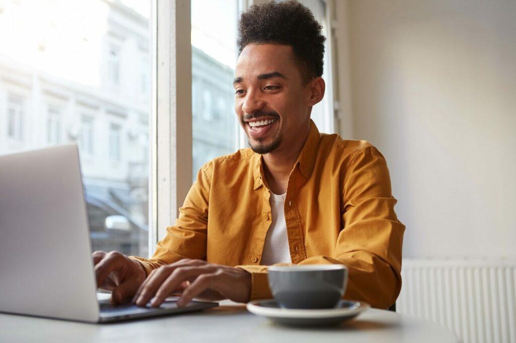 Homem jovem trabalhando feliz na frente do computador | Club Coworking
