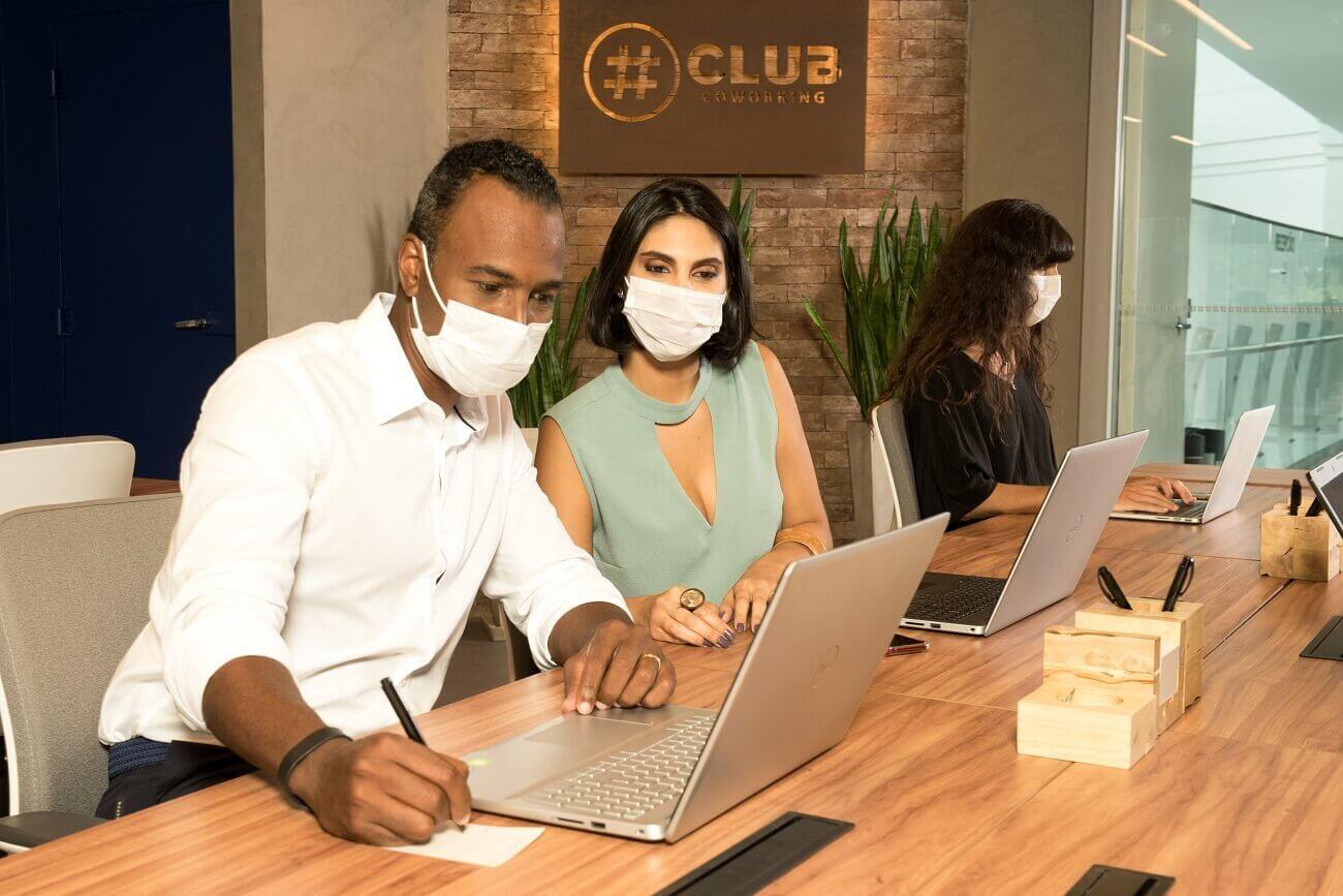 Equipe de homem e mulher trabalha em espaço coworking em modelo de trabalho híbrido