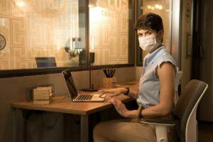 Mulher trabalhando em espaço coworking com estrutura e design que ajudam produtividade