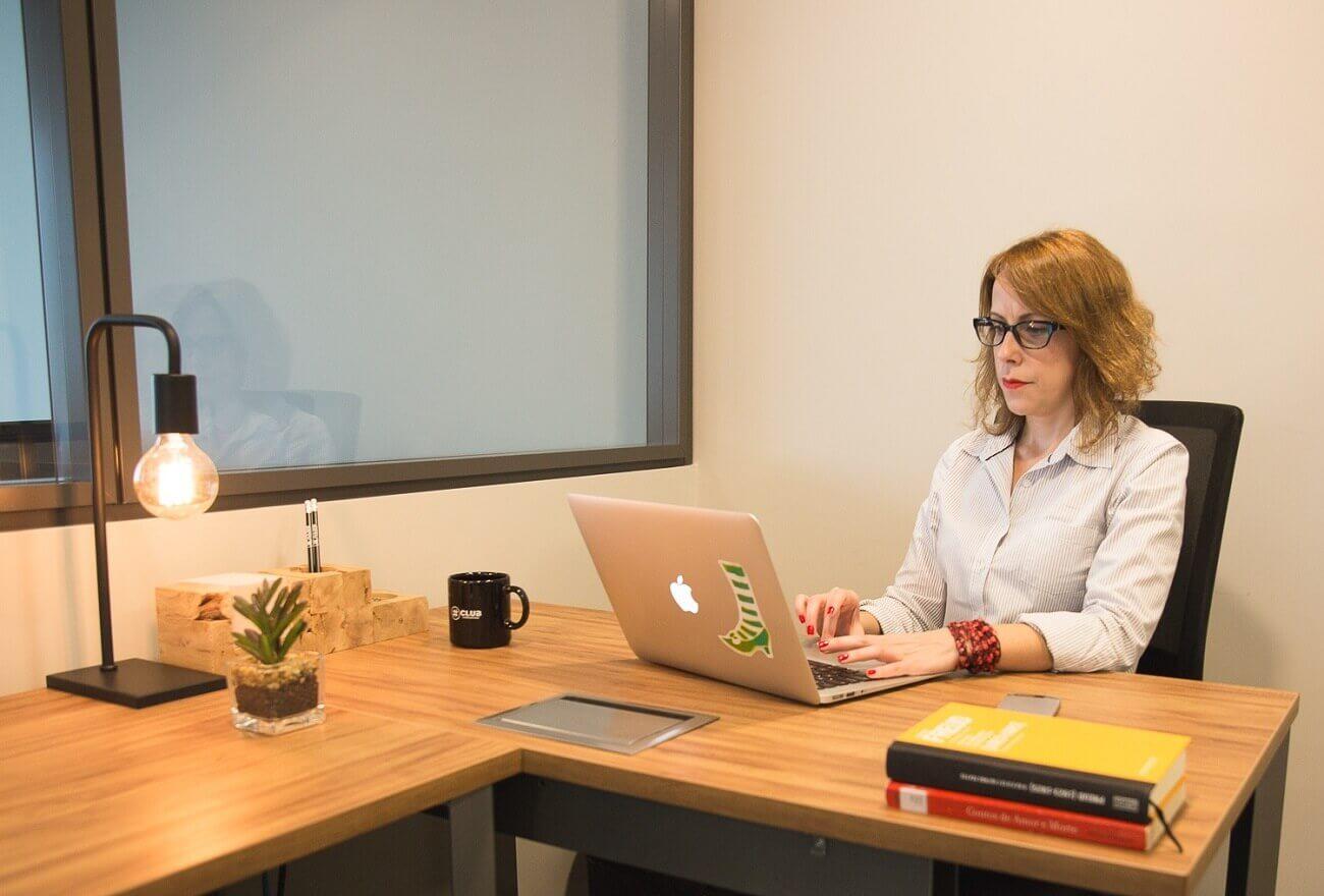 Mulher trabalhando na frente do computador em trabalho híbrido em espaço coworking | Club Coworking