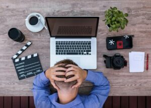 Homem com a mão na cabeça enquanto tem dificuldade de trabalhar em frente ao computador