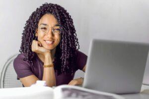Mulher trabalha sorrindo no ambiente de trabalho em frente a um computador