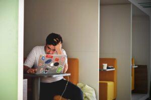 Homem trabalha cansado na frente do computador