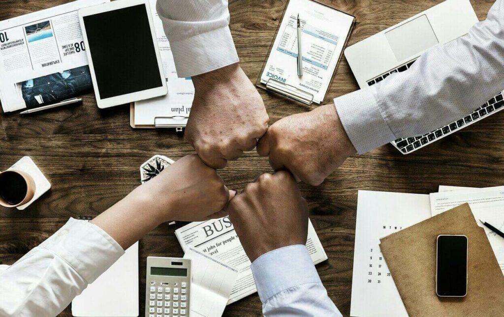 Mãos fechadas unidas em ambiente de escritório employer branding